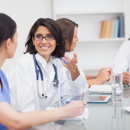Two doctors speaking with two nurses during meeting